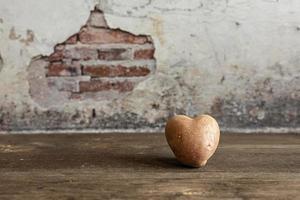 Patata roja en forma de corazón sobre fondo vintage.El concepto de agricultura, cosecha, vegetarianismo. día de San Valentín. comida cuadrada y fea. foto