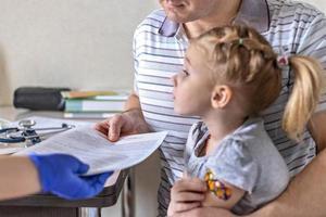 niña con su padre en el consultorio del médico en la clínica. vacunado contra el coronavirus. el médico le pasa los documentos al papá de la niña. el concepto de vacunación del covid-19 foto