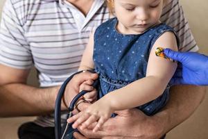 vacunación de una niña en brazos de su papá en el consultorio del médico contra el coronavirus. yeso adhesivo divertido para niños. vacuna contra covid-19, gripe, enfermedades infecciosas. foto