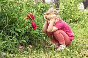 una niña sosteniendo su cabeza pensativa, sentada junto a un macizo de flores en el jardín de peonías rosas foto