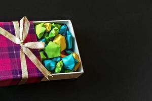 Caja de regalo de color con lazo de raso con estrellas de papel origami sobre fondo negro. regalos para las fiestas. foto