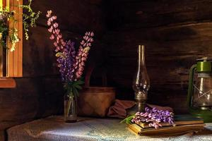 Still life of vintage items and a bouquet of lupins on a table by the window in an old village house. photo