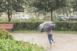 A little girl is having fun running around with an umbrella in the heavy rain. Rainy day photo