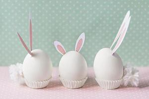 White chicken eggs with bunny ears and tails on bed flowers background. A family. Happy Easter holiday concept photo