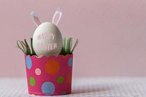 White chicken egg with bunny ears in an eco-friendly pink paper tray, box. Happy Easter holiday concept. English text Happy Easter photo