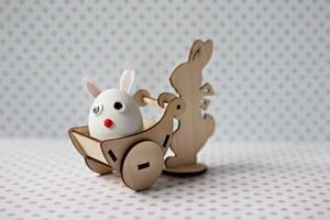 A wooden rabbit carries a cart with an egg with bunny ears. Easter decorations photo