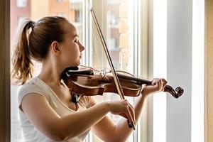 A young girl, a musician, plays the violin on the background of a window photo