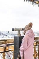 A young girl looks through coin-operated binoculars on the observation deck overlooking the city from a height at sunset. Winter, snowfall photo