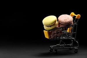 Coloridos macarons de galletas de almendra o macarrones en carrito de compras sobre fondo negro. minimalismo, sombras nítidas foto