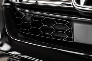 Grid of white sports car. The radiator grille. Metal texture. chrome grille of a big powerful. Front of the car. Radiator grill of luxury sports car. Plastic or metal grill. radiator grill photo
