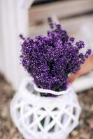 Pile of lavender flower bouquets on a wooden old bench in a summer garden. bouquet of lavender photo