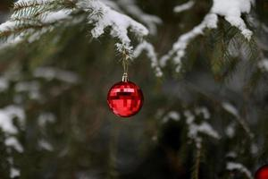 Christmas ball with a garland hanging on Christmas tree. Merry Christmas and Happy New Year. selective focus photo