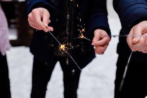 people burn Bengal lights. Sparkler background. Christmas and new year sparkler holiday background. photo