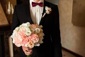 Close-up of a cropped frame is a tender bouquet of roses in the hands of a groom. photo