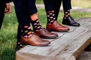 Fashion men footwear. guys wearing leather shoes and colorful socks on wooden bench. selective focus. photo