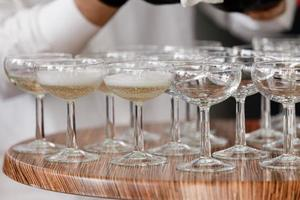 sparkling wine, champagne in glasses on the wooden table. waiter in black gloves pours alcohol into glasses in the restaurant. selective focus photo