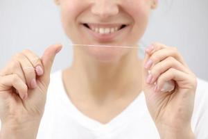 Dental hygiene and care. Dental floss. Young healthy woman face with beauty smile. Beautiful girl. Person healthcare. photo