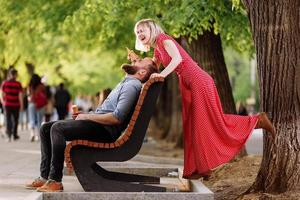smiling hipsters couple having fun and eating ice cream in the city. stylish young man with beard is sitting on a wooden bench and blonde woman in red dress woman fools around and plays with him photo