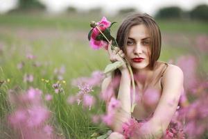 hermoso retrato de una niña con flores rosas. niña en el campo de flores. peonía burdeos, paisaje foto