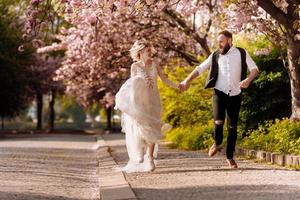 Happy stylish man with beard and woman with long dress are having fun in spring blossoming sakura park. Newly wedded hipsrers couple in the park. Just married. run in the park and hold hands. photo