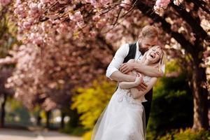 hermosa joven pareja, hombre con barba y mujer rubia abrazándose en el parque de la primavera. pareja elegante cerca del árbol con sakura. concepto de primavera. moda y belleza foto