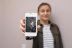Mujer joven frustrada que sostiene el teléfono móvil con el cristal de la pantalla roto. la pantalla del teléfono necesita reparación. aislado sobre fondo gris. enfoque selectivo en smartphone foto