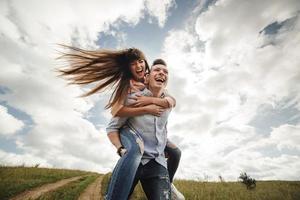 Pareja joven loca divirtiéndose emocionalmente, besándose y abrazándose al aire libre. amor y ternura, romance, familia, emociones, diversión. divirtiéndonos juntos foto