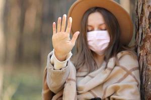 mujer en máscara protectora médica detener el virus al aire libre en el bosque. contaminación del aire, concepto ambiental enfoque selectivo foto