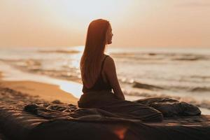 lovely morning sunrise at sea, silhouette of the girl at sunset. woman relaxes by the sea. meditation concept photo