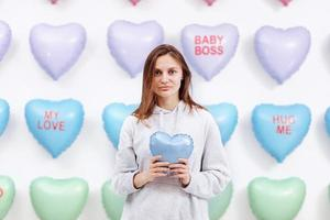 beautiful young woman holds the blue balloon in the form of a heart. many hearts background. valentines day. baby shower. selective focus photo
