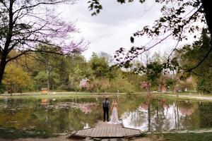 young stylish groom and bride in luxury long dress standing in front of the lake in park with blooming cherry or sakura blossoms on background. Wedding spring day photo