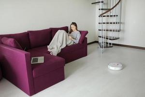 robot cleaner cleans. girl resting at home on the couch, while the robot vacuum cleaner. concept time for yourself. smart House. modern girl optimizes her time. robots concept. selective focus photo