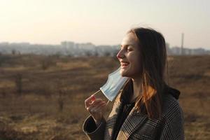 sonriente joven quita la mascarilla médica de la cara. terminación de la cuarentena, coronavirus. mujer protegiendo del coronavirus. COVID-19. tiempo feliz, aire fresco foto