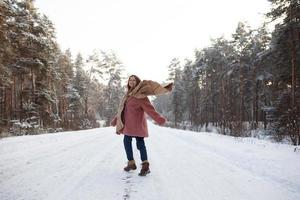 Young pretty stylish woman having fun in the winter snowy forest in motion. photo