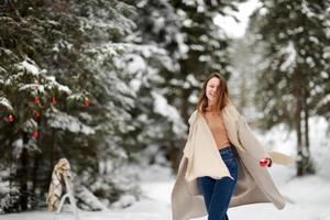 happy young woman in winter day outdoors in forest. background of tree branches in the snow and decorated with Christmas decorations. photo