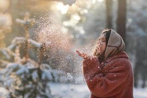 Beautiful, stylish and young girl, blowing the snow from her hands in winter forest. Christmas holiday. photo