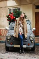 Beautiful girl in city. happy young woman standing near a retro car decorated with Christmas tree. Cold happy winter day. Holidays, christmas, winter, love, beauty concept photo