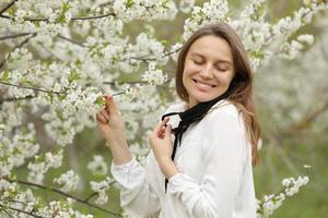 happy beautiful girl took off her medical mask to breathe in the smell of flowers. A girl in a mask stands in blossoms. the end of quarantine photo