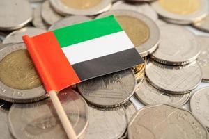 Pila de monedas con la bandera de los Emiratos Árabes Unidos sobre fondo blanco. bandera sobre fondo blanco. foto