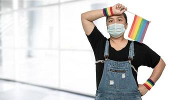 Asian lady wearing mask for protect covid-19 virus holding rainbow flag, symbol of LGBT pride month celebrate annual in June social of gay, lesbian, bisexual, transgender, human rights. photo