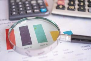 Magnifying glass on charts graphs paper. Financial development, Banking Account, Statistics, Investment Analytic research data economy, Stock exchange trading, Business office company meeting concept. photo
