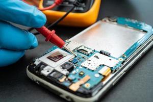 técnico que repara el interior del teléfono móvil con un soldador. circuito integrado. el concepto de datos, hardware, tecnología. foto