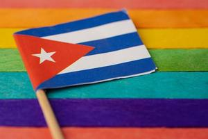 Cuba flag on rainbow background flag symbol of LGBT gay pride month  social movement rainbow flag is a symbol of lesbian, gay, bisexual, transgender, human rights, tolerance and peace. photo
