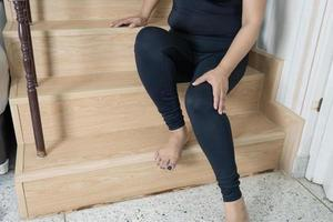 Asian middle-aged lady woman patient fall down the stairs because slippery surfaces and pain her knee. photo