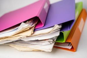 File Folder Binder stack of multi color on table in office. photo