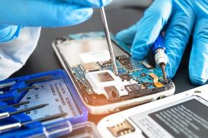 Technician repairing inside of mobile phone by soldering iron. Integrated Circuit. the concept of data, hardware, technology. photo