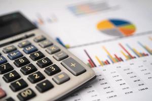 calculadora en tabla y papel cuadriculado. finanzas, cuentas, estadísticas, datos de investigación analítica y concepto de reunión de empresa comercial foto