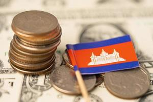 Stack of coins with Cambodia flag on US dollar banknotes background. photo