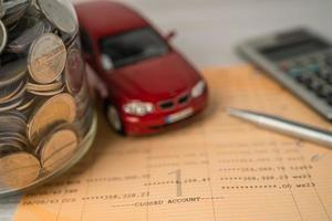 Car and calculator with coins on bookbank background, Car loan, Finance, saving money, insurance and leasing time concepts. coins, Car loan, Finance, saving money, insurance and leasing time concepts. photo
