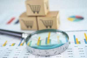 Magnifying glass and shopping cart logo on box with graph background. Banking Account, Investment Analytic research data economy, trading, Business import export transportation online company concept. photo
